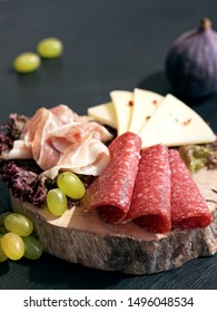 Sliced slices of salami, bacon, cheese located on a sheet of salad on a wooden board. Grapes and figs. Close-up.