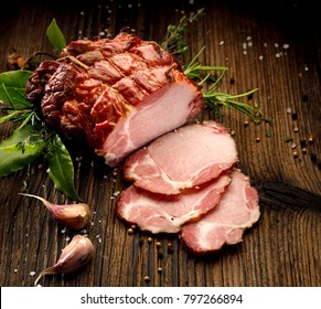 Sliced smoked gammon on a wooden  table with addition of fresh  herbs and aromatic spices.   Natural product from organic farm, produced by traditional methods