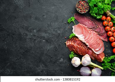 Sliced smoked meat with spices and herbs. On a black wooden background. Top view. Free space for your text.