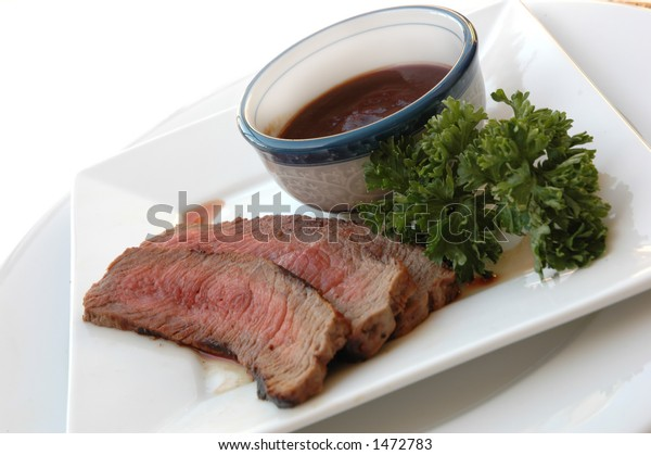 Sliced steak on a plate with barbecue sauce