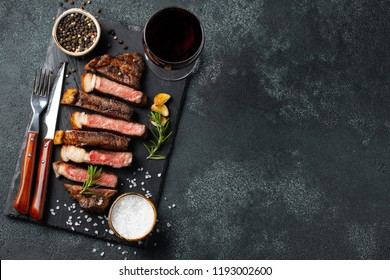 Sliced steak Striploin, grilled with pepper, garlic, salt and thyme served on a slate chopping Board with a glass of red wine on a dark stone background. Top view with copy space