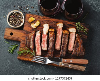 Sliced steak Striploin, grilled with pepper, garlic, salt and thyme served on a wooden chopping Board with a glass of red wine on a dark stone background. Top view