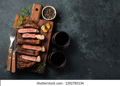 Sliced steak Striploin, grilled with pepper, garlic, salt and thyme served on a wooden chopping Board with a glass of red wine on a dark stone background. Top view with copy space