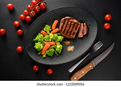 sliced steak with vegetables served on a black plate