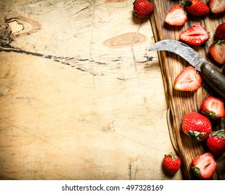 Sliced strawberries with the old knife on the Board. On wooden background.