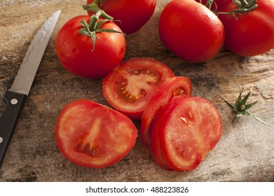 Sliced succulent red tomatoes beside serrated knife and other uncut ones on a rustic wooden table