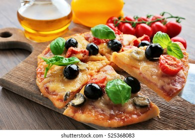 Sliced tasty pizza and fresh cherry tomatoes on wooden cutting board