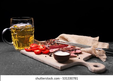 Sliced tasty steak with tomatoes and beer on cutting board
