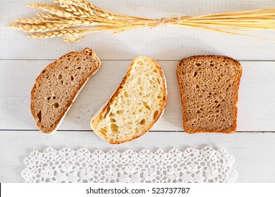 Sliced three types of bread on white wooden table.