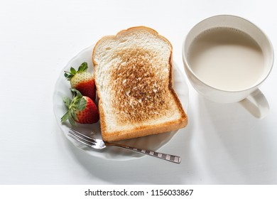 sliced toast bread, fresh strawberry with milk in the morning.