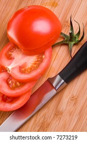 Sliced tomato with knife on wooden cutting board.