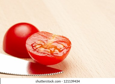Sliced tomato with serrated knife on wooden chopping block