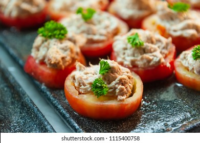 Sliced tomatoes stuffed with tuna paste.