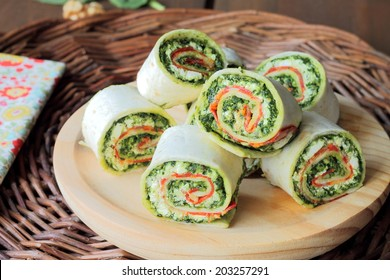Sliced tortilla wrap with lunchmeat, ricotta and pesto sauce