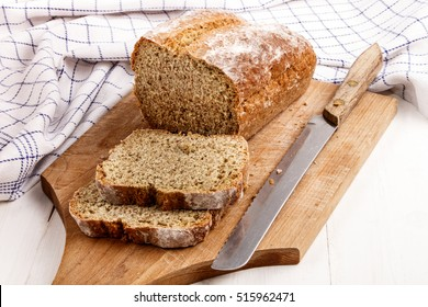 sliced traditional irish soda bread on a wooden board with bread knife