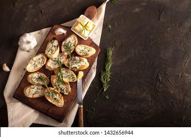 Traditionelles Toastbrot mit Butter, Oliven, Knoblauch und Kräutern auf einem Schnittbrett, Serviette und dunklem Tisch mit Kopienraum. Draufsicht.