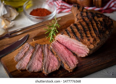 sliced tri tip seak marinated with santa maria sauce  on wooden cutting board
