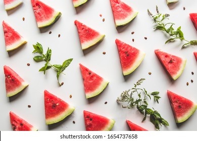 sliced triangular slices of ripe red watermelon with seeds with green mint leaves, lime