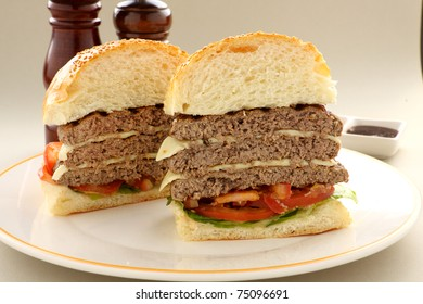 Sliced triple decker beef and cheese burger with salad ready to serve.