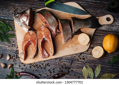 sliced trout on a Board on a wooden table with lemon and seasonings. Fresh red fish for cooking