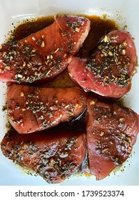 Sliced tuna in soy sauce sprinkled with spices before roasting