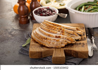 Sliced turkey on a cutting board for Thanksgiving or Christmas dinner table