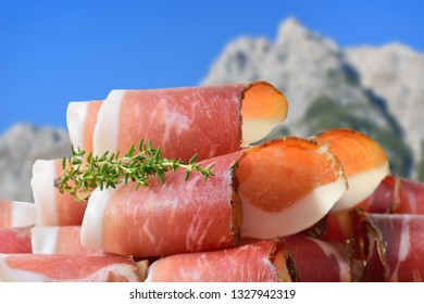 Sliced typical South Tyrolean bacon lying in front of mountains of the alps
