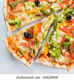 Sliced vegetarian pizza with broccoli, green beans, olives and tomatoes. Top view, close-up
