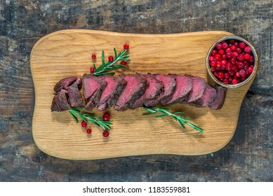 Sliced venison steak on wooden board with lingonberries - top view
