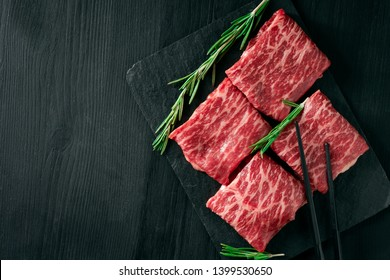 Sliced wagyu marbled beef for yakiniku on plate on black background, Premium Japanese meat and stick, top view and copy space