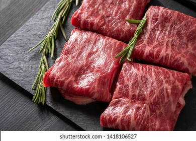 Sliced wagyu marbled beef for yakiniku on plate on black background, Premium Japanese meat, close up