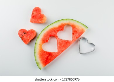 Sliced watermelon with cutting accessory in the shape of heart on white background, flat lay.