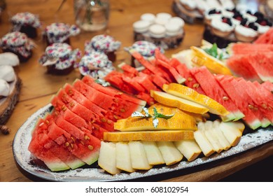 sliced watermelon and malon on a dish on a wooden table