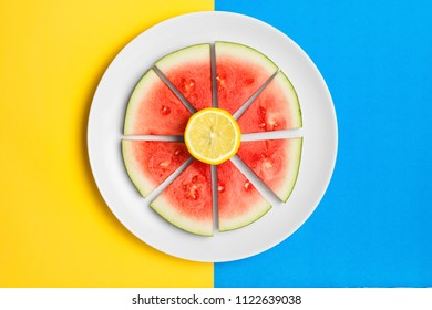 Sliced watermelon on a plate with fresh lemon. Flat lay image