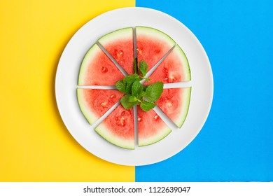 Sliced watermelon on a plate with fresh mint leaves. Flat lay image