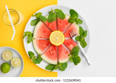Sliced watermelon on plate with mint and lemon, ready to eat.