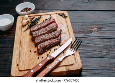 Sliced well-done grilled beef steak on wooden cutting board with rosemary and spices and cutlery, close up. Appetizing meat