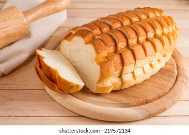 Sliced white bread on wood plate.
