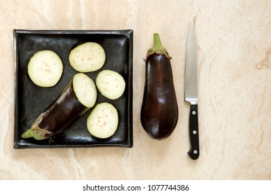 Sliced and whole eggplant aubergine with knife on marble table