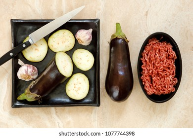 Sliced and whole eggplant aubergine and minced beef with knife on marble table for greek moussaka