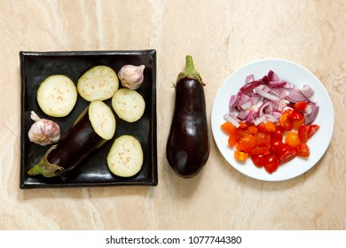 Sliced and whole eggplant aubergine with onions and tomatoes with knife on marble table for greek moussaka