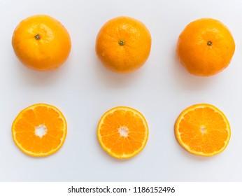 Sliced and whole orange on white background and arranged around of frame