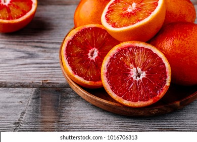 Sliced and whole ripe juicy Sicilian Blood oranges on wooden background. Selective focus