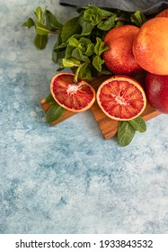 Sliced and whole ripe juicy Sicilian blood oranges on wooden cutting board with mint, blue concrete background. Selective focus. Top view.