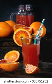 Sliced and whole Sicilian Blood oranges and glass of fresh red orange juice over old wooden table. Dark rustic style.