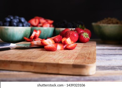 Sliced and whole strawberries on cutting board with knife, low key lighitng and horizontal orientation.