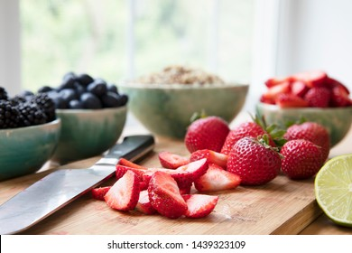 Sliced and whole strawberries on cutting board with knife, horizontal orientation.