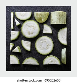 Sliced zucchini, laid out in a square form. Background with fresh zucchini on a black background in a white frame. Vegetables isolated. View from above.