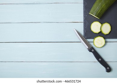 A sliced zucchini on a slate and wooden counter top background forming a page border