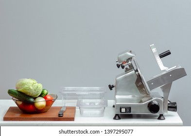 slicer for cutting food on the table with vegetables and canteens for storage